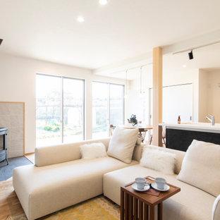 Exemple d'un salon moderne avec un mur blanc, un sol en bois brun, un poêle à bois, un manteau de cheminée en carrelage, un téléviseur fixé au mur, un sol gris et un plafond en papier peint.