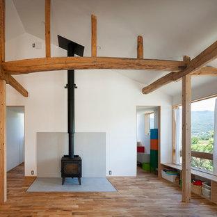 他の地域のカントリー風おしゃれなLDK (白い壁、無垢フローリング、薪ストーブ、コンクリートの暖炉まわり、グレーの床) の写真