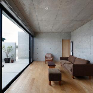 他の地域のモダンスタイルのおしゃれなファミリールーム (グレーの壁、淡色無垢フローリング、茶色い床) の写真