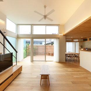 Bild på ett mellanstort minimalistiskt allrum med öppen planlösning, med vita väggar, ljust trägolv, en väggmonterad TV och brunt golv