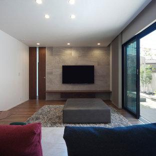 他の地域のモダンスタイルのおしゃれなリビング (マルチカラーの壁、濃色無垢フローリング、壁掛け型テレビ、茶色い床) の写真