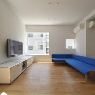 他の地域のモダンスタイルのおしゃれなリビング (白い壁、無垢フローリング、壁掛け型テレビ、茶色い床) の写真