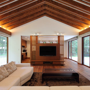 Design ideas for a medium sized world-inspired formal open plan living room in Other with white walls, plywood flooring, no fireplace, a wall mounted tv and brown floors.