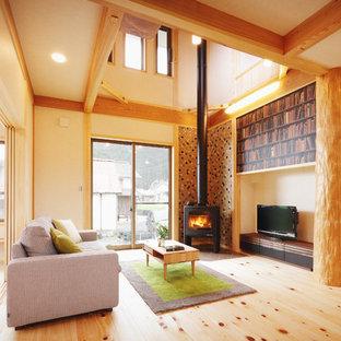 他の地域のアジアンスタイルのおしゃれなLDK (黄色い壁、淡色無垢フローリング、薪ストーブ、金属の暖炉まわり、据え置き型テレビ、ベージュの床) の写真