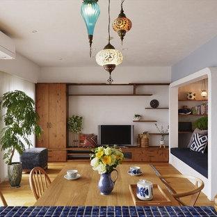 Exemple d'un salon méditerranéen ouvert avec un mur multicolore, un sol en bois brun, un téléviseur indépendant et un sol marron.