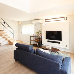他の地域のモダンスタイルのおしゃれなリビング (白い壁、塗装フローリング、壁掛け型テレビ、ベージュの床) の写真