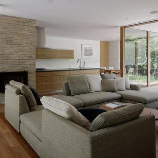 他の地域のモダンスタイルのおしゃれなLDK (白い壁、無垢フローリング、標準型暖炉、レンガの暖炉まわり、オレンジの床) の写真
