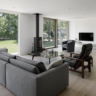 他の地域のモダンスタイルのおしゃれなLDK (フォーマル、白い壁、淡色無垢フローリング、薪ストーブ、金属の暖炉まわり、壁掛け型テレビ、グレーの床) の写真