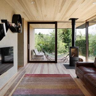 他の地域のアジアンスタイルのおしゃれなLDK (マルチカラーの壁、無垢フローリング、薪ストーブ、壁掛け型テレビ、茶色い床、金属の暖炉まわり) の写真