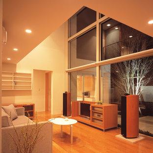 他の地域のコンテンポラリースタイルのおしゃれなリビング (ベージュの壁、無垢フローリング、据え置き型テレビ、茶色い床) の写真