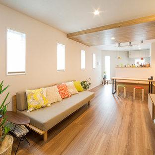 他の地域の小さいモダンスタイルのおしゃれなLDK (マルチカラーの壁、無垢フローリング、壁掛け型テレビ、茶色い床) の写真