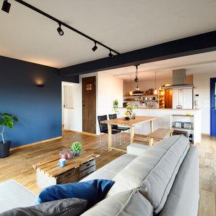 東京都下の北欧スタイルの居間の画像 (青い壁、無垢フローリング、据え置き型テレビ、茶色い床)