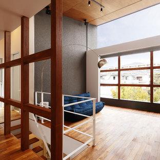 他の地域のコンテンポラリースタイルのリビング・居間の画像 (マルチカラーの壁、無垢フローリング、据え置き型テレビ、茶色い床)