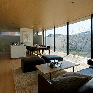 Cette photo montre un salon moderne ouvert avec un mur blanc, un sol en contreplaqué, un sol beige et un téléviseur dissimulé.