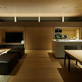 На фото: парадные, открытые гостиные комнаты в стиле модернизм с белыми стенами, полом из фанеры, скрытым ТВ и бежевым полом