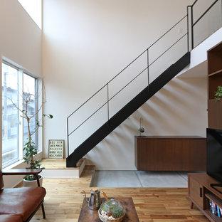他の地域の中くらいのラスティックスタイルのおしゃれなLDK (白い壁、無垢フローリング、据え置き型テレビ、茶色い床) の写真