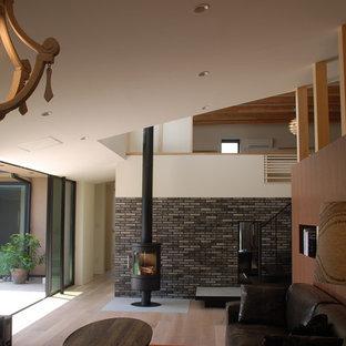 Esempio di un soggiorno design con pareti bianche, parquet chiaro, camino sospeso, cornice del camino in mattoni e TV autoportante