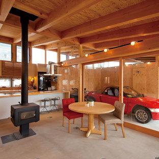 他の地域の小さいアジアンスタイルのおしゃれなリビング (コンクリートの床、薪ストーブ、木材の暖炉まわり、茶色い壁) の写真