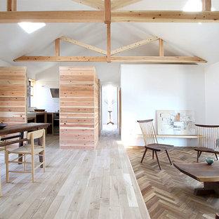 Ejemplo de salón abierto, rural, con paredes blancas, suelo de madera clara, estufa de leña, marco de chimenea de hormigón, televisor colgado en la pared y suelo blanco