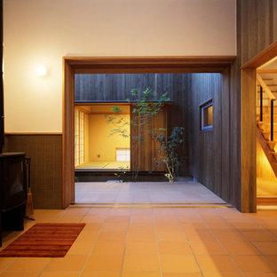 Idee per un soggiorno etnico con pareti bianche, pavimento in terracotta, camino bifacciale e pavimento marrone