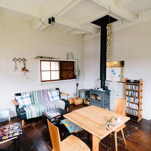 Diseño de salón abierto, nórdico, pequeño, sin televisor, con paredes grises, suelo de madera oscura y estufa de leña