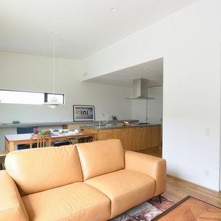 他の地域の中くらいのコンテンポラリースタイルのおしゃれなリビング (白い壁、淡色無垢フローリング、壁掛け型テレビ、茶色い床) の写真