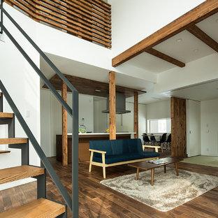 Immagine di un soggiorno etnico di medie dimensioni e aperto con pareti bianche, pavimento in legno massello medio, nessun camino e TV autoportante