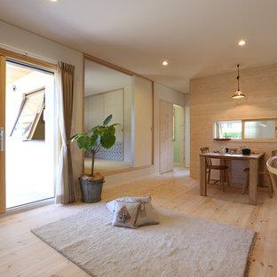 他の地域のアジアンスタイルのおしゃれなLDK (白い壁、無垢フローリング、据え置き型テレビ、ベージュの床) の写真