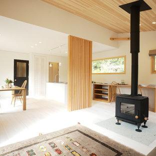 Diseño de salón abierto, moderno, con paredes blancas, suelo de madera clara, estufa de leña, marco de chimenea de piedra, televisor independiente y suelo blanco