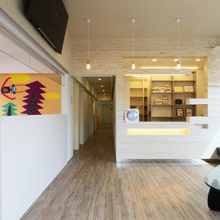 他の地域のコンテンポラリースタイルのおしゃれなリビング (白い壁、塗装フローリング、壁掛け型テレビ、グレーの床) の写真
