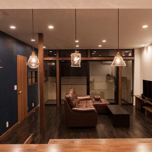Mittelgroße, Offene Industrial Bibliothek mit blauer Wandfarbe, Sperrholzboden, Wand-TV und schwarzem Boden in Sonstige