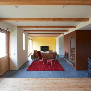 コンテンポラリースタイルのおしゃれなリビング (黄色い壁、標準型暖炉、グレーの床) の写真