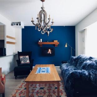 Ispirazione per un soggiorno stile americano di medie dimensioni e aperto con pareti blu, pavimento in compensato, camino sospeso, cornice del camino in legno, nessuna TV e pavimento grigio