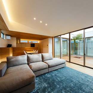 Photo of a mid-sized modern formal open concept living room in Other with white walls, no fireplace, a wall-mounted tv, brown floor and plywood floors.