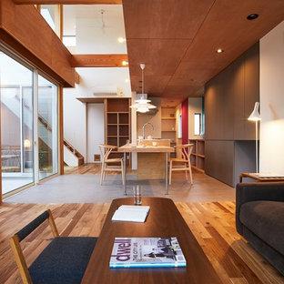 Mittelgroßes, Offenes Modernes Wohnzimmer ohne Kamin mit brauner Wandfarbe, braunem Holzboden, freistehendem TV und braunem Boden in Sonstige