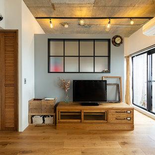 他の地域のインダストリアルスタイルのおしゃれなLDK (白い壁、据え置き型テレビ、茶色い床) の写真