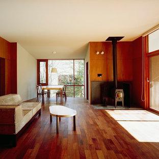他の地域の小さいモダンスタイルのおしゃれなLDK (茶色い壁、濃色無垢フローリング、薪ストーブ、コンクリートの暖炉まわり、テレビなし、茶色い床) の写真