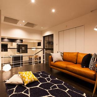 他の地域の小さいミッドセンチュリースタイルのおしゃれな独立型リビング (白い壁、合板フローリング、壁掛け型テレビ、黒い床) の写真