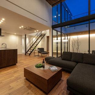 他の地域の広いモダンスタイルのおしゃれなLDK (白い壁、茶色い床、濃色無垢フローリング、板張り天井、パネル壁) の写真