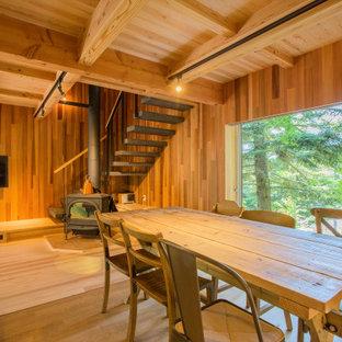 Ispirazione per un soggiorno moderno aperto con parquet chiaro, stufa a legna, cornice del camino piastrellata, TV a parete, pareti marroni e pavimento marrone