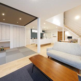 他の地域の広いおしゃれなLDK (白い壁、淡色無垢フローリング、ベージュの床) の写真