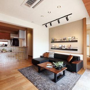 Modelo de salón abierto, de estilo zen, con paredes blancas, suelo de madera en tonos medios y suelo marrón