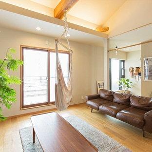 他の地域の大きい北欧スタイルのおしゃれなLDK (白い壁、無垢フローリング、薪ストーブ、タイルの暖炉まわり、据え置き型テレビ、茶色い床) の写真