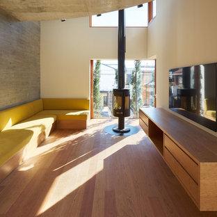 東京23区のコンテンポラリースタイルのおしゃれなリビング (ベージュの壁、無垢フローリング、吊り下げ式暖炉、壁掛け型テレビ、茶色い床) の写真