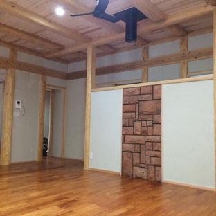 他の地域の巨大なアジアンスタイルのおしゃれなリビング (薪ストーブ、レンガの暖炉まわり、テレビなし、オレンジの床) の写真