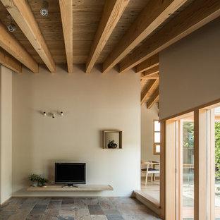 Immagine di un soggiorno etnico con pareti beige, nessun camino, TV autoportante e pavimento con piastrelle in ceramica