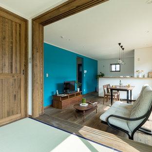 他の地域のアジアンスタイルのおしゃれなリビング (青い壁、無垢フローリング、据え置き型テレビ、茶色い床) の写真