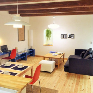 This is an example of a scandinavian open concept living room in Other with white walls, medium hardwood floors and brown floor.