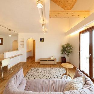 他の地域の地中海スタイルのおしゃれなLDK (白い壁、無垢フローリング、暖炉なし、茶色い床、フォーマル、据え置き型テレビ) の写真