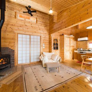 札幌のカントリー風おしゃれなリビング (茶色い壁、無垢フローリング、薪ストーブ、レンガの暖炉まわり、茶色い床) の写真